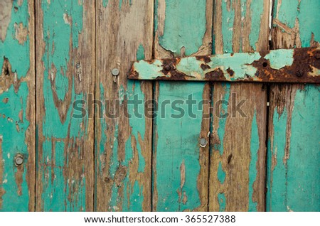 My rustic blue front door - Wooden old planks in aqua color from a barn door. This rustic background has been composed with a rusty hinge at the left upper part of the frame. - stock photo