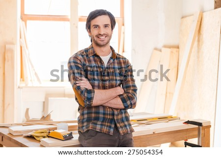 My workshop is my world! Happy young male carpenter keeping arms crossed and leaning at the wooden table with diverse working tools laying on it - stock photo