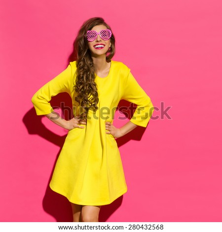 My World In Pink Sunglasses. Beautiful young woman in yellow mini dress and pink heart shaped sunglasses posing with hands on hip. Three quarter length studio shot on pink background. - stock photo