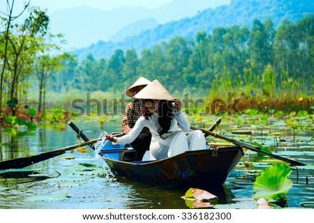 MYDUC, VIETNAM - October 18, 2015: A girl in traditional costume rowing boat in the flooded forest in MYDUC, VIETNAM. MYDUC is a district about 60 km from Hanoi.