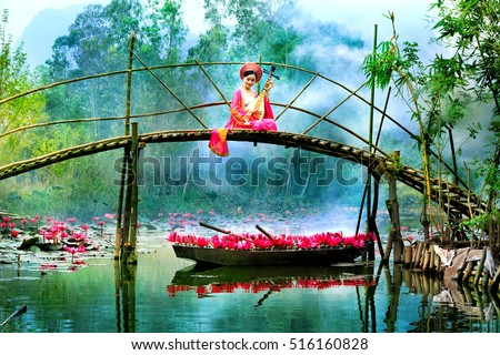 MYDUC, VIETNAM - OCTOBER 22, 2016: girl in traditional costume rowing boat and playing traditional instruments in the flooded forest in MYDUC, VIETNAM. MYDUC is a district about 60 km from Hanoi.