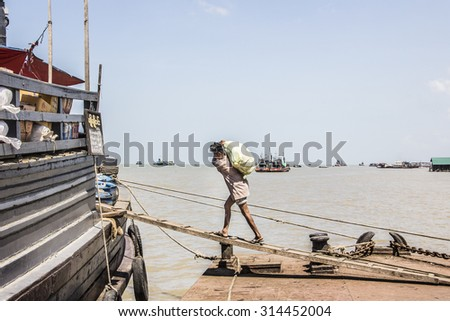 MYEIK, MYANMAR - FEBRUARY 20, 2015: A porter is carrying a load over a plank up to the ship. In the port of Myeik in the south of Myanmar. In the background are fisher boats.