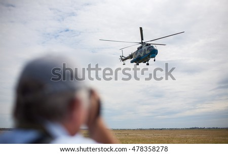 MYKOLAIV, UKRAINE JULY 22, 2016: Photographer taking pictures of landing of the MI-8 flying helicopter during the international military exercises Sea Breeze launched in Odessa and Mykolayiv regions.