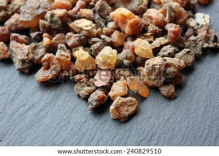 Myrrh incense tears (myrrhae gummi from kenia) in tears on a grey slate stone background - stock photo