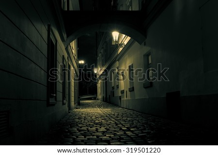 mysterious alley with lanterns in Prague at night - stock photo