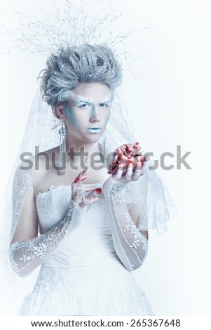 Mysterious and unusual girl with face art in the form of the Snow Queen. Girl holding a human heart in the blood. The girl closed her eyes. The concept of eternal winter. - stock photo