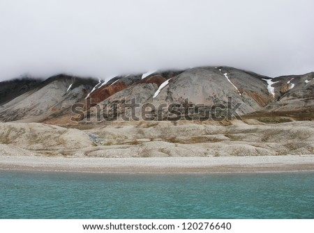 Mysterious arctic view - blue waters of Recherchefjorden and barren shore with melting snow and heavy fog, Spitsbergen archipelago (Svalbard island), Norway, Greenland Sea, Atlantic ocean  - stock photo