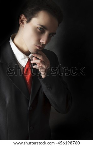 mysterious business man in suit with red tie on black background