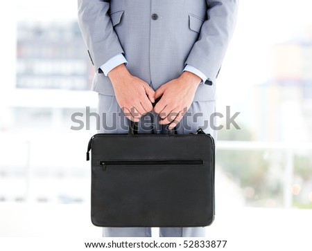 Mysterious businessman holding a briefcase in the office - stock photo