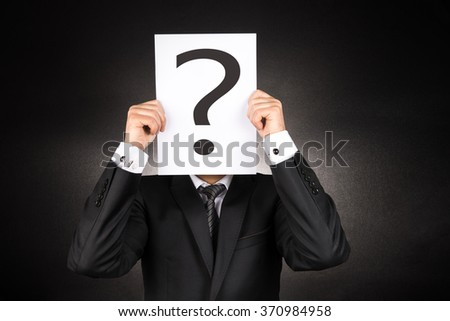 Mysterious Businessman holding question mark - stock photo