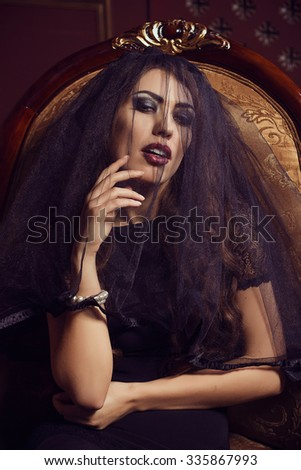 Mysterious come-hither woman model in black transparent lace veil, evening dress sitting in vintage chair. Beauty. Fashion make-up smoky eyes. Luxury. Sexuality. Seduction. Sensuality. Italian style.