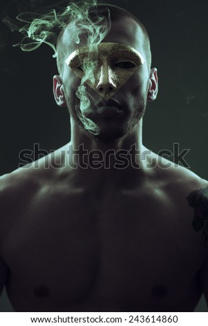 Mysterious cult concept. Portrait of handsome boy with golden triangle mask. Arty make-up, smoke near his face. Close up. Vogue style. Studio shot - stock photo