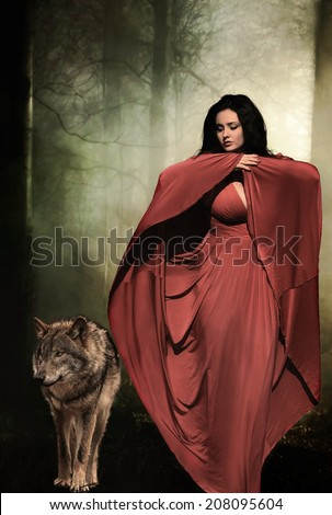 Mysterious dark woman in forest at night with wolf. Book cover - stock photo
