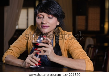 Mysterious fancy brunette young woman thinking while holding a glass of red wine at the bar - stock photo