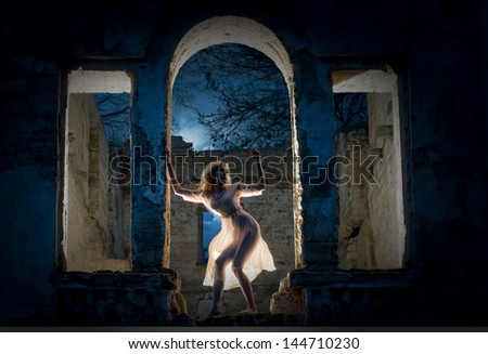 Mysterious female figure standing in the arc of the ruined building - stock photo