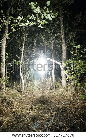 Mysterious Glowing White Diamond Shaped Anomaly Floating Above Grassy Secluded Forest Clearing Illuminating Surrounding Trees at Night