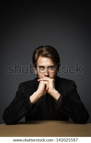 Mysterious handsome young man sitting at a table with his chin in his hand and an enigmatic expression