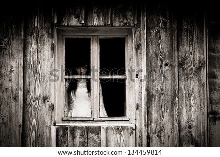 Mysterious horror woman staring out the window. - stock photo