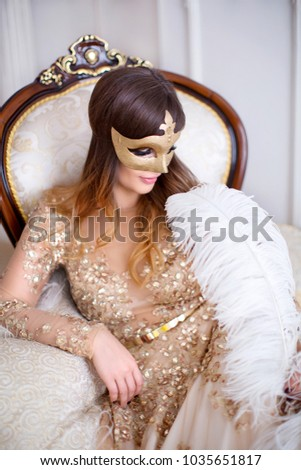 Mysterious ledy in masquerade venetian golden mask, holding in her hand a long white feather