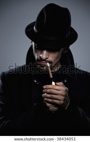 Mysterious man lighting a cigarette - stock photo