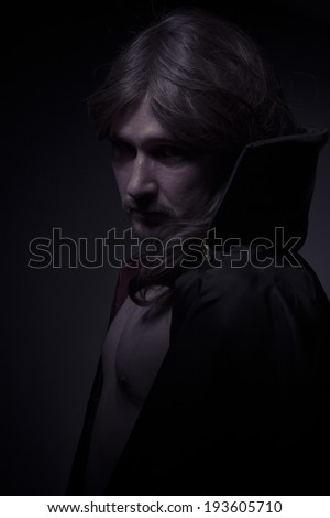 Mysterious man with long hair and black coat - stock photo