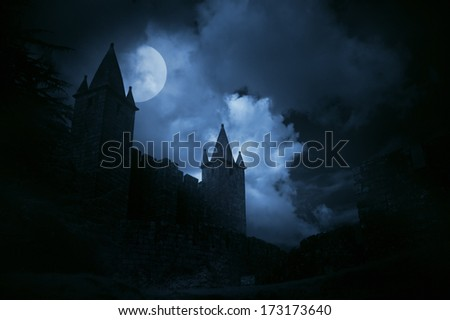 Mysterious medieval castle in a misty full moon. Added some digital noise. - stock photo