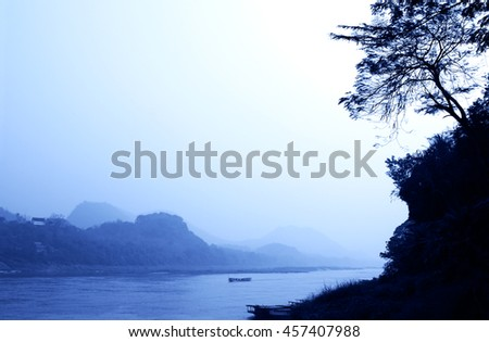 Mysterious morning landscape with mountains and river Mekong, near to Luang Prabang, Laos. Toned in blue color