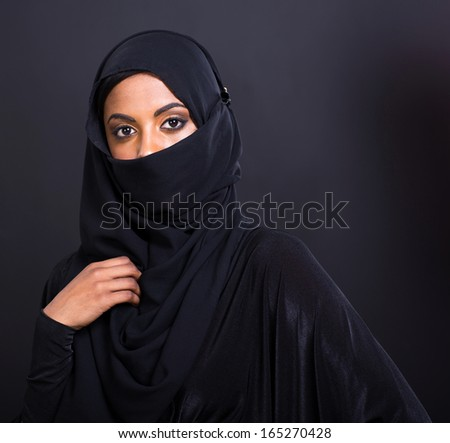 mysterious muslim woman isolated on black background - stock photo