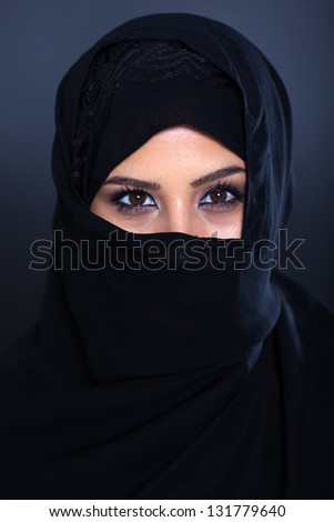 mysterious Muslim woman on black background - stock photo