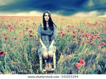 Mysterious portrait of young beautiful woman sitting on stool in a poppy field and looking at camera, summer nature outdoor. Toned. - stock photo