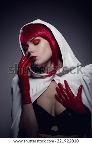 Mysterious sensual vampire girl with red lips wearing white hooded jacket, artistic shot   - stock photo