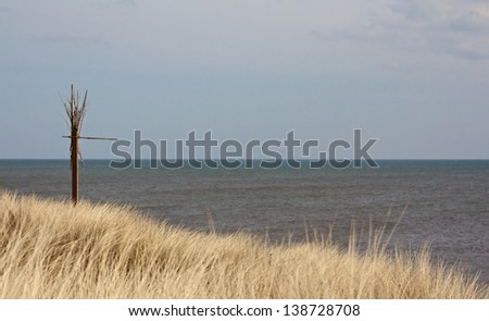 Mysterious sign between beach grass at the North Sea coast of Sylt island, Germany - stock photo
