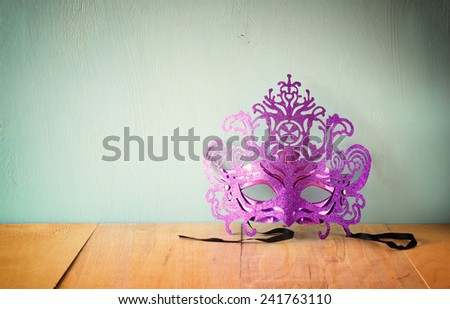 Mysterious Venetian masquerade mask on wooden table. retro filtered image - stock photo