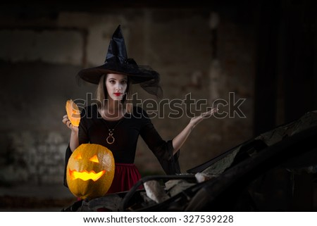 Mysterious witch performing magic with carved pumpkin