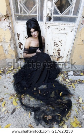 Mysterious woman dressed in black gothic dress. - stock photo