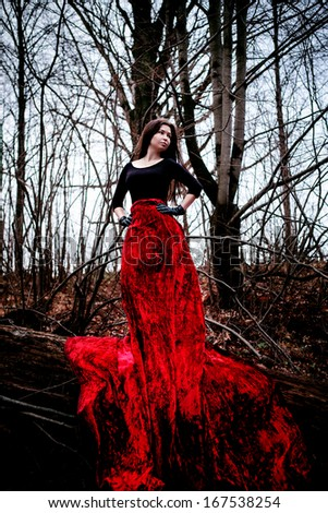 Mysterious woman or witch in long red dress standing in dark forest - stock photo