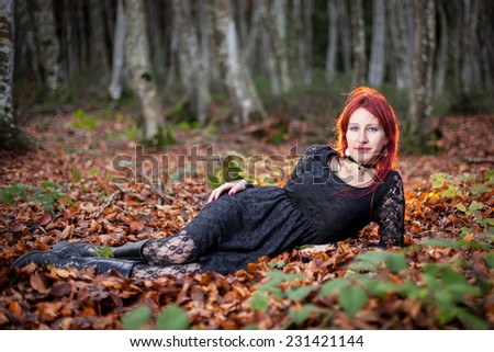 Mysterious woman portrait in gothic dress  lying on foliage