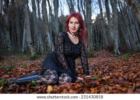 Mysterious woman portrait in gothic dress  sitting on foliage with  forest background