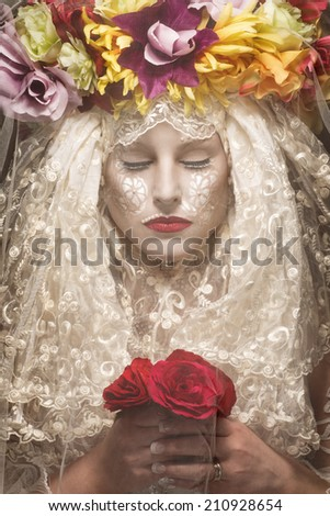 Mysterious woman with flowers behind veil - stock photo