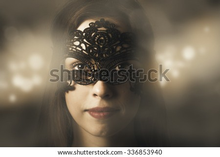 Mystery and fantasy concept on the face of a beauty model wearing dark black venetian carnival mask at new year party celebration on magic light background. Masquerade ball woman - stock photo
