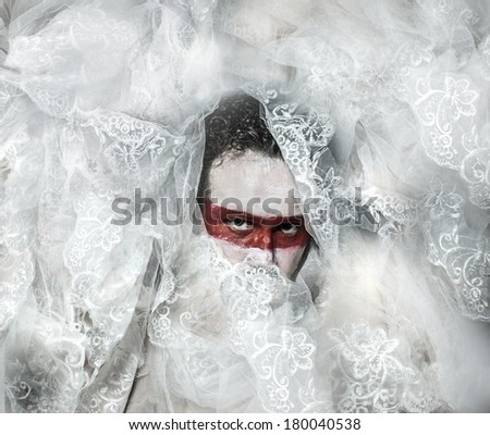 Mystery, covered with white lace veil, red makeup man mask - stock photo