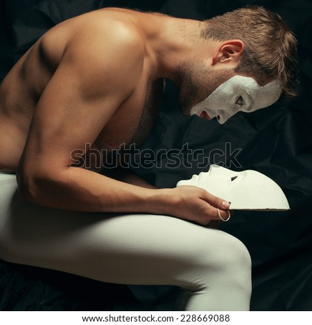 Mystery double concept. Arty portrait of circus performer in tights holding and looking at venetian mask (volto bianco), posing over black cloth. Muscular body and perfect tan. Studio shot - stock photo