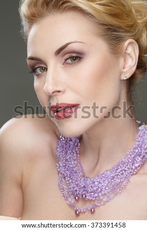 Mystery look. Vertical cropped closeup of a stunning mature woman looking seductively to the camera
