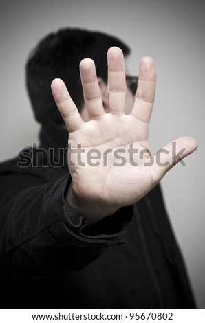 Mystery man holding up hand and looking away - stock photo