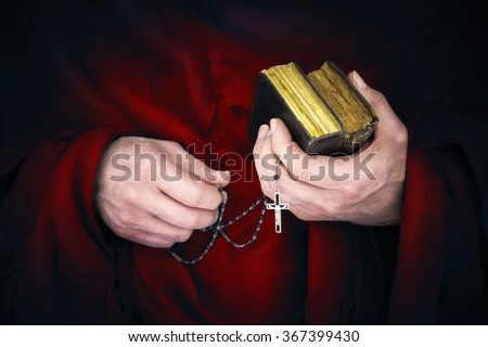 Mystery monk with a cape holding bibles and a black rosary in his hands - stock photo