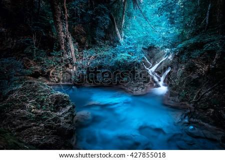Mystery night at deep tropical rain forest with flowing cascade waterfall. Fantasy jungle landscape.  Erawan, National Park Kanchanaburi, Thailand - stock photo