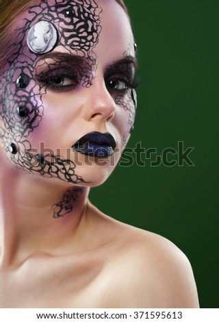 Mystic girl. Portrait of a young female model wearing creative lace makeup with crystals and a cameo