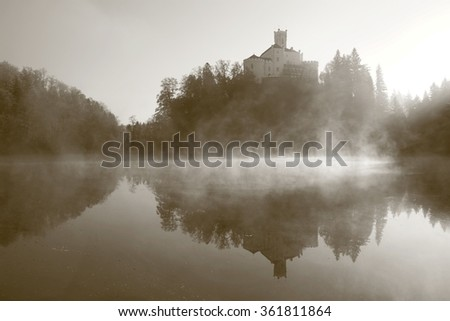 Mystic morning atmosphere with castle on the hill and foggy lake - stock photo