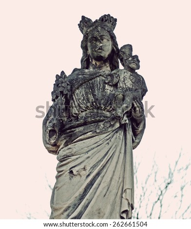 Mystic old stone statue of the Blessed Mother and Jesus is partly broken head on the headstone in the cemetery in Ukraine in vintage style - stock photo