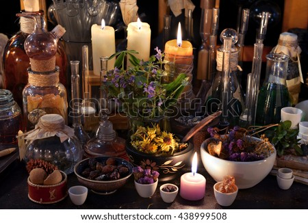 Mystic still life with dry herbs, old bottles, candles and flasks. Old pharmacy, esoteric or alchemic concept. Black magic and occult objects, alternative medicine or homeopathic still life - stock photo